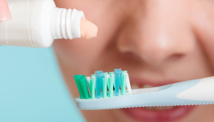 Woman Putting Toothpaste On Toothbrush